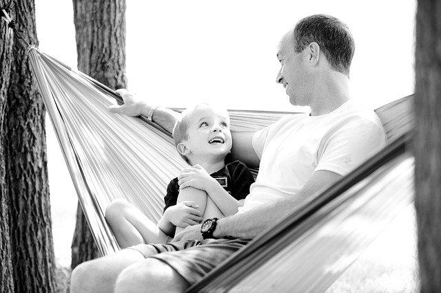 far og barn i hengekøya snakker om livet og har det fint sammen